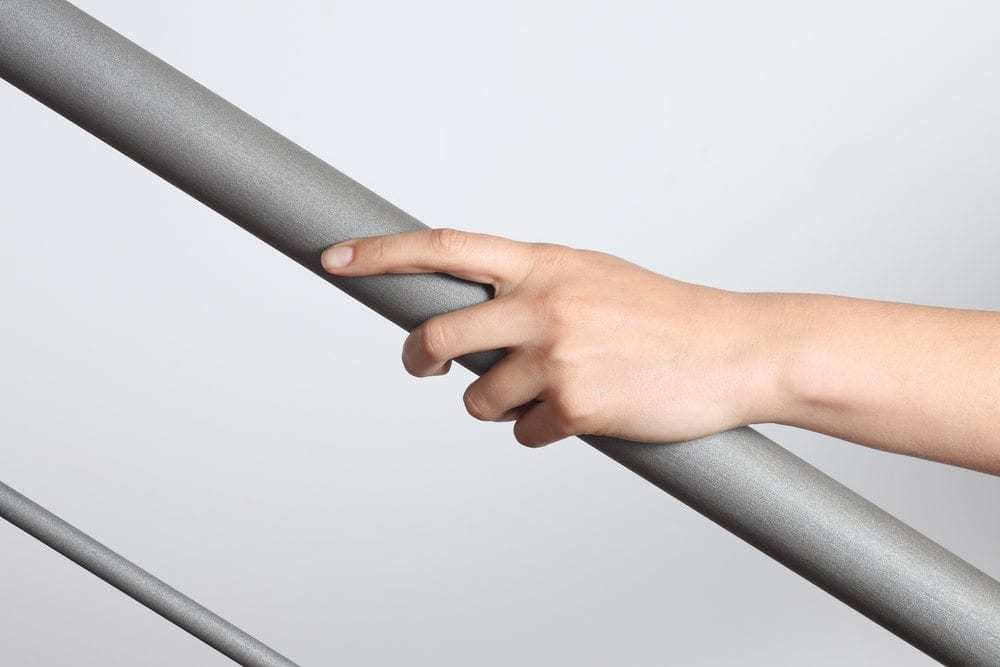 Woman hand using a railing to go upstairs with a light grey background