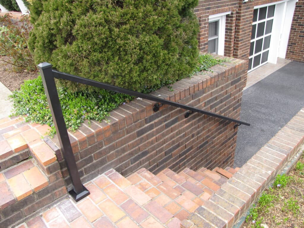 Downward view of brick steps with aluminum handrail on one side